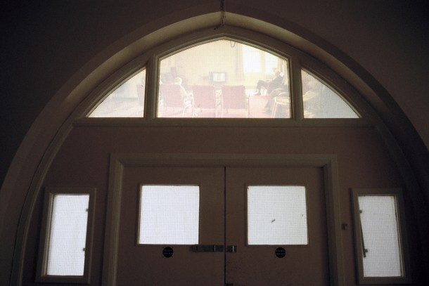 Back projection of empty hospital wards on window above ward doors.