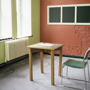 Writing desk, chair and vandalised wall